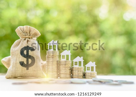 Saving for a first house deposit or a first time home buyer program concept : House models on stacks of coins, depicts saving for a down payment on a real estate or tangible / non depreciation assets #1216129249