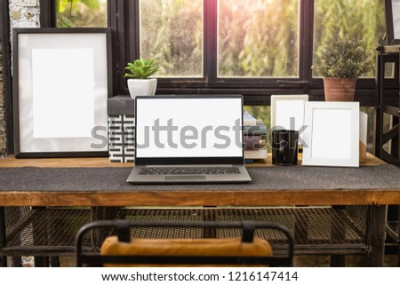 computer Notebook or laptop with blank screen and empty picture frame on a vintage wooden desktop at home with garden background
