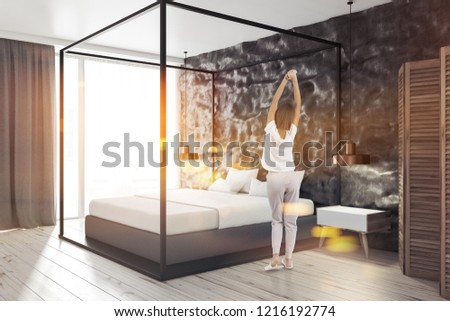 Woman in the corner of modern bedroom with crude black walls, concrete floor, master bed and loft windows. Toned image #1216192774