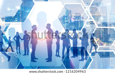 Silhouettes of business people shaking hands and walking over cityscape background. Concept of partnership. Toned image double exposure #1216204963
