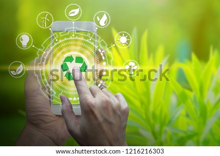Hand holding smartphone with environment Icons over the Network connection on nature background, Technology ecology concept. #1216216303