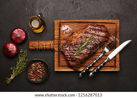 Grilled striploin beef steak on wooden board with vegetables, herbs and spices on dark stone background. Top view #1216287013