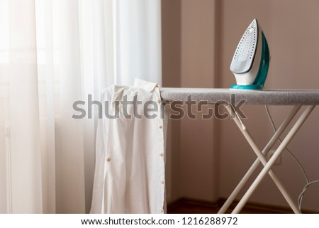 Ironed shirt hanging from an ironing board next to a hot iron. Selective focus on the iron #1216288972