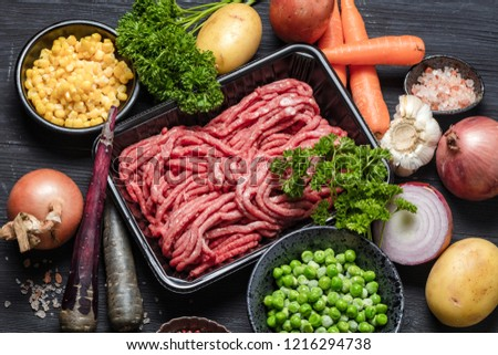 Raw minced meat in container surrounded by ingredients for shepherds pie , green peas, yellow corn, carrot, onion and seasonings, on black background, top view. Horizontal composition  #1216294738