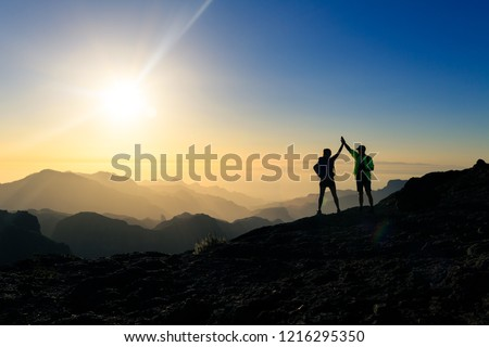 Couple hikers celebrating success in sunset mountains, accomplish with arms up outstretched. Young man and woman looking at beautiful inspirational landscape view, Gran Canaria Canary Islands. #1216295350
