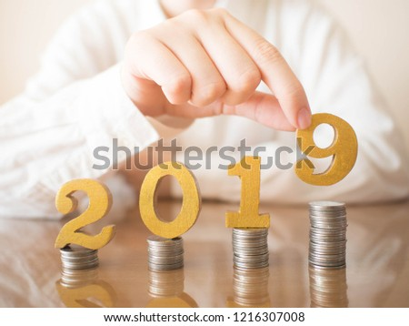 2019 New year saving money and financial planning concept. Female hands putting gold wooden number 2019 on stack of coins. Creative idea for business growth, tax payment, investment and banking. #1216307008