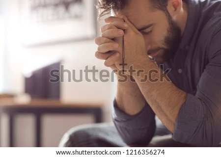 Religious young man praying to God at home Royalty-Free Stock Photo #1216356274