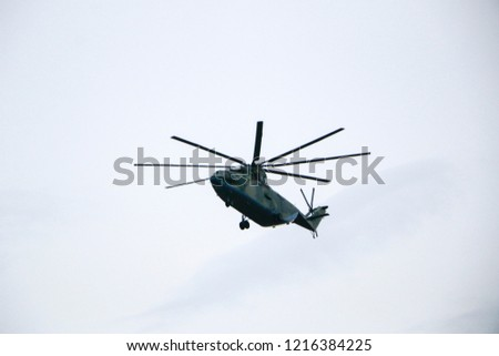 large military helicopter hovers in  sky. A camouflaged helicopter flies at high speed. #1216384225