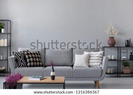 Industrial living room with simple grey sofa and metal furniture, real photo with copy space on the wall #1216386367