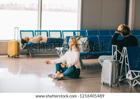 young woman meditating in lotus position while waiting flight in airport terminal #1216405489