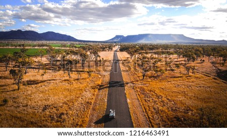 4wd Road Trip jeep journey to Ayers Rock through the rural Outback Australia valleys in desert land with mountains in the background and eucalyptus trees and some farm land #1216463491
