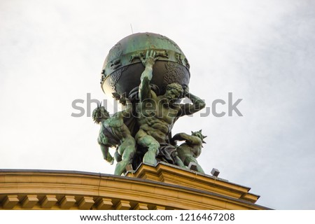 The titan called Atlas is carrying the world on his shoulders. Greek mythotology figure as  part of the historical train station roof built in 1888 in Frankfurt, Germany.  Royalty-Free Stock Photo #1216467208