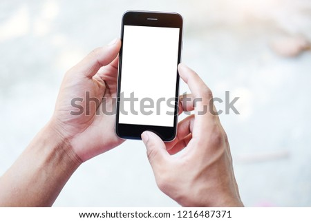 Cropped shot view of man hands holding smart phone with blank copy space screen for your text message or information content, female reading text message on cell telephone during in urban setting. #1216487371