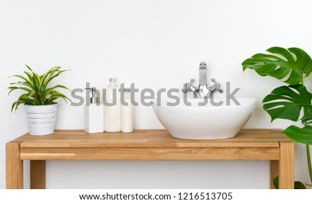 Bathroom wooden table with washbasin, faucet, plants and soap bottles #1216513705