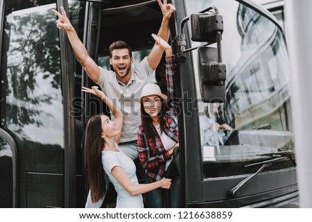 Young Smiling People Traveling on Tourist Bus. Group of Happy Friends Standing Together in Doors of Tour Bus. Traveling, Tourism and People Concept. Happy Travelers on Trip. Summer Vacation Royalty-Free Stock Photo #1216638859