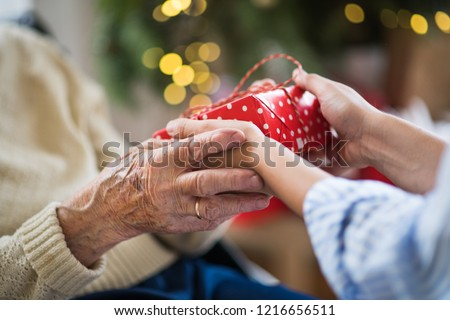 Close-up of hands of senior and young woman holding a present at Christmas. #1216656511