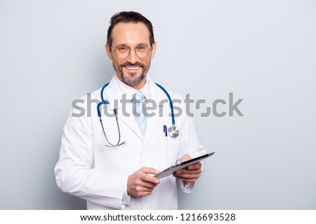 Portrait of half turn brunet hair bristle pharmacist man look at camera stand isolated on light gray background half turn make beaming toothy smile hold tablet in hands #1216693528