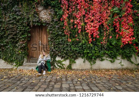 PRAGUE, CZECH REPUBLIC - 26 october 2018: Woman reading before the gardendoor. In the autumn. #1216729744