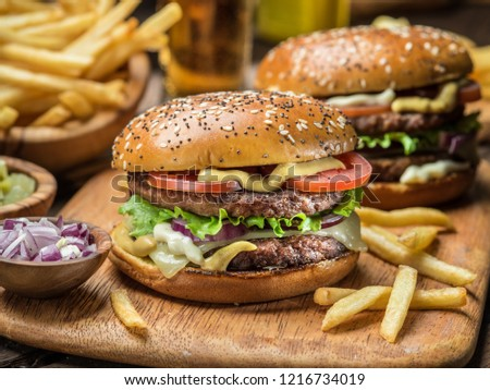 Hamburgers and French fries on the wooden tray. #1216734019