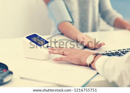 Adult woman having blood pressure test during visit at female doctor's office #1216755751