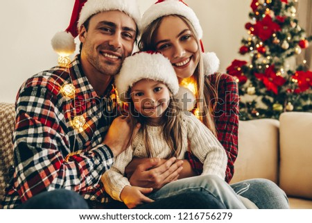 Christmas Family. Happiness. Portrait of dad, mom and daughter in Santa hats sitting on a couch at home near the Christmas tree, all are smiling #1216756279