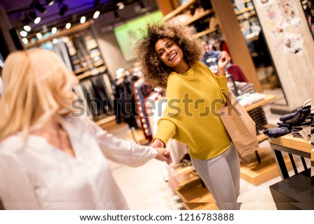 Two multiracial young women choosing clothes from new collection in department store #1216783888