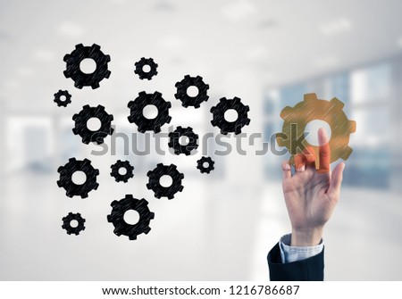 Hand of businesswoman touching glowing icon on screen and office at background #1216786687