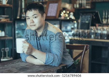 Handsome Asian guy relaxing in coffee house and looking at camera. Content young man enjoying morning coffee. Coffee culture concept #1216789606