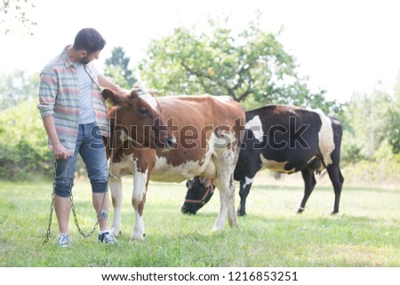 Male farmer checking on his herd on his farm #1216853251