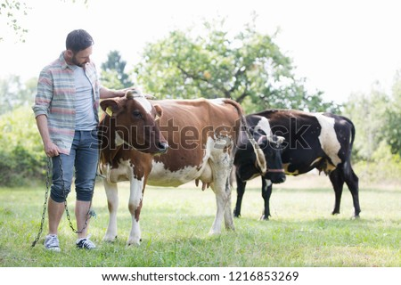 Male farmer checking on his herd on his farm #1216853269