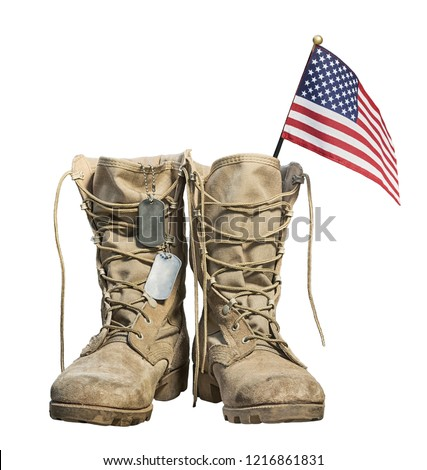 Old military combat boots with the American flag and dog tags, isolated on white background. Memorial Day or Veterans day concept. Royalty-Free Stock Photo #1216861831