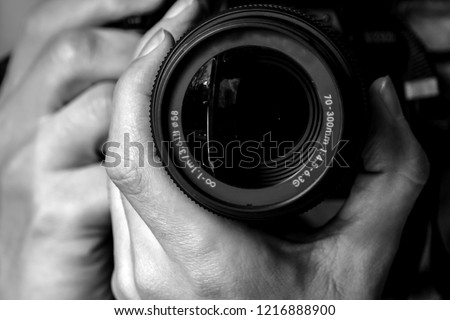 Black and white Closeup of dslr camera lens holding by a professional photographer looking front and  taking photo with blurred background