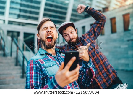 Two friends showing sincere emotions of joy about victory in online lottery. Men being happy winning a bet in online sport gambling application with football stadium on the background.  #1216899034