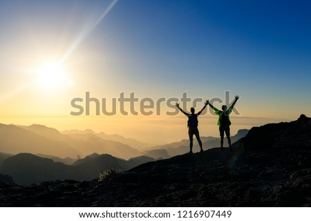 Couple hikers success and trust in mountains, accomplish with arms up outstretched. Young man and woman looking at beautiful inspirational landscape view, Gran Canaria Canary Islands. #1216907449