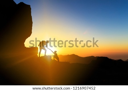 Teamwork couple helping hand trust help silhouette in mountains, sunset. Team of climbers man and woman hikers, help each other on top of mountain, climbing together, inspiring sunset on Gran Canaria #1216907452