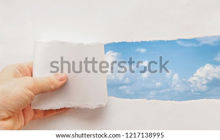 blue sky and white clouds behind torn paper #1217138995