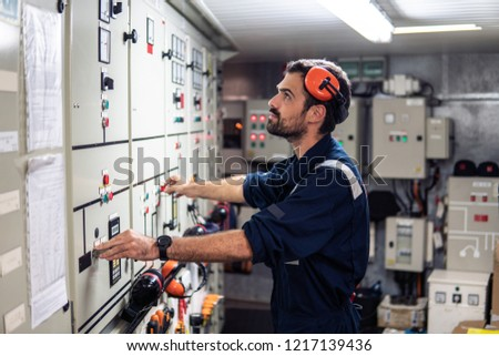 Marine engineer officer in engine control room ECR. Seamen's work. He starts or stops main engine of ship Royalty-Free Stock Photo #1217139436
