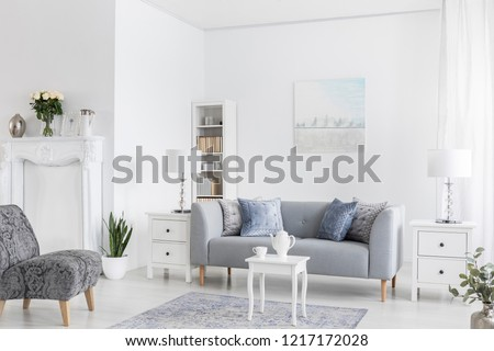 Grey sofa between white cabinets with lamps in flat interior with armchairs and table on carpet. Real photo #1217172028