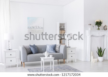 Table on carpet in front of grey settee in white living room interior with lamps and poster. Real photo #1217172034