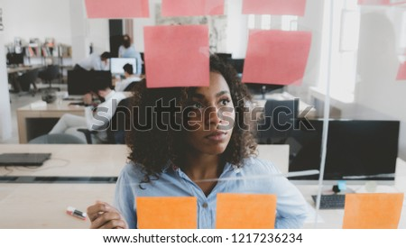 African American black employee looking onto a glass wall with sticky notes, framework for managing work, scrum methodology Royalty-Free Stock Photo #1217236234