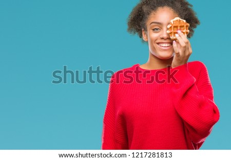 Young beautiful afro american woman eating waffle over isolated background with a happy face standing and smiling with a confident smile showing teeth #1217281813