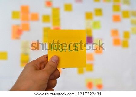 A hand is holding a orange agile sticker and there is a Kanban board of agile methodology on the background, which is a developing trend in Information Technology (IT) business.  #1217322631