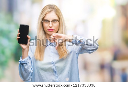 Young beautiful blonde business woman showing screen of smartphone over isolated background with angry face, negative sign showing dislike with thumbs down, rejection concept #1217333038
