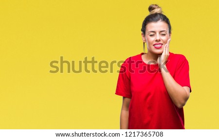 Young beautiful woman over isolated background touching mouth with hand with painful expression because of toothache or dental illness on teeth. Dentist concept. #1217365708