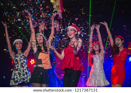 Cheerful smilling happily young people showered with confetti on club party. #1217387131