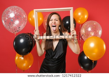 Funny young girl in little black dress celebrating showing tongue holding picture frame on bright red background air balloons. St. Valentine's Day Happy New Year birthday mockup holiday party concept