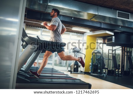 Male running on treadmill at the gym #1217462695