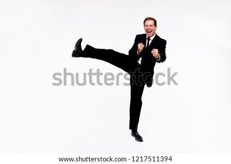 Karate! Full length of handsome man in suit looking at camera with smile and doing karate while standing against white background  Royalty-Free Stock Photo #1217511394