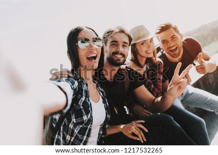Young Smiling People Sitting in Park taking Selfie. Group of Young Friends with Backpacks Sitting Together taking Selfie by Using Smartphone. Travelers Enjoying Summer. People and Friendship Concept #1217532265