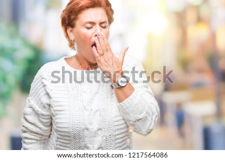Atrractive senior caucasian redhead woman wearing winter sweater over isolated background bored yawning tired covering mouth with hand. Restless and sleepiness. #1217564086